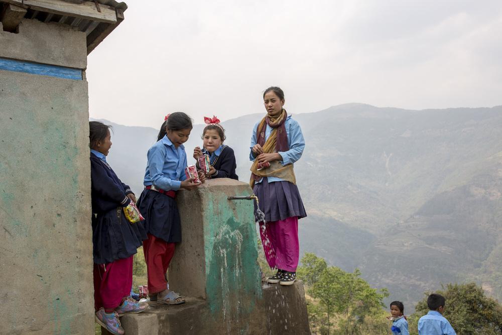 School girls gather around a drinking fountain