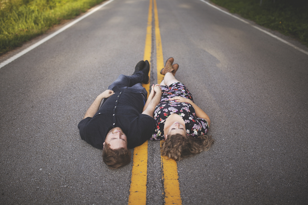 laying in street holding hands engagement photographer in kentucky