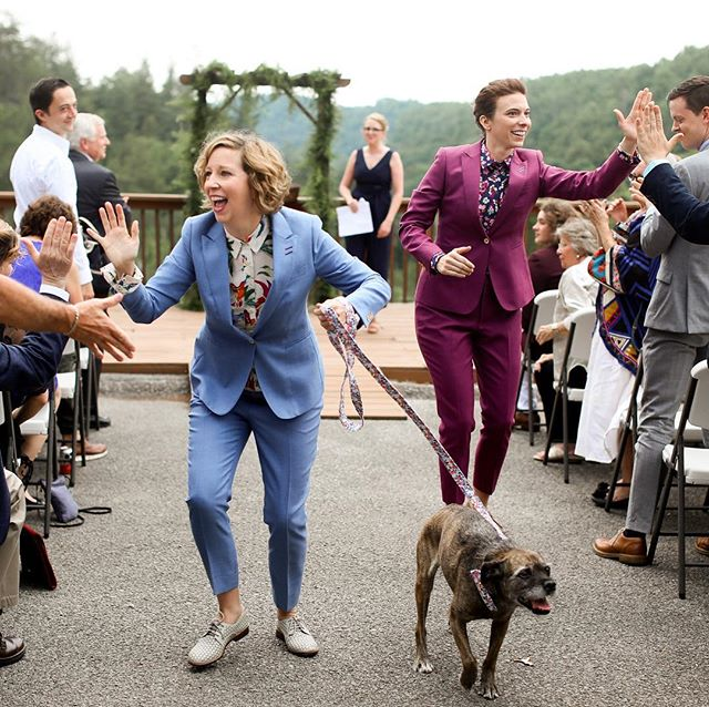 Two ladies, in custom suits, exiting their Kentucky wedding with pup in tow. 😍 // Daring Tales of Darling Bones Wedding & Engagement Photography . . . #kentuckybride #kentuckywedding #huffpostido #love #married #shesaidyes #ido #theville #sharethelex #rainyweddingday #weddingday  #kentucky #engagement #thatsdarling #adventure #rrg #liveauthentic #loveauthentic #engaged #bride #groom #lexington #louisville #weddingphotographer #engagementphotographer #southernbride #bourbonbride #bourbon #MakersMark