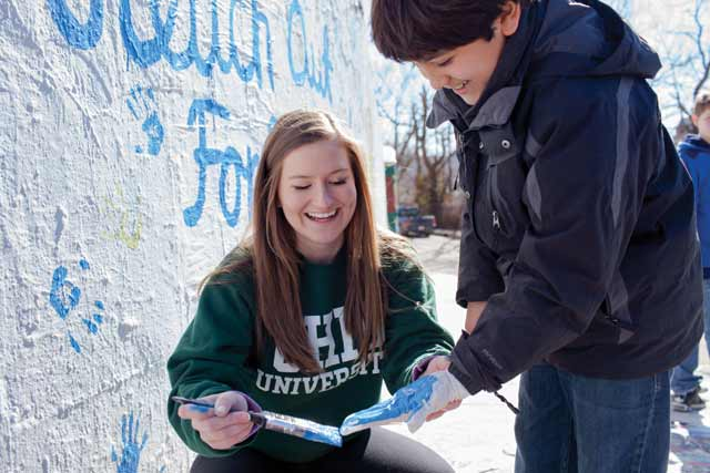 OU student Marisa Dockum paints local student's hand so he could make his mark against bullying for Reach Out for Friendship. (Megan Westervelt)