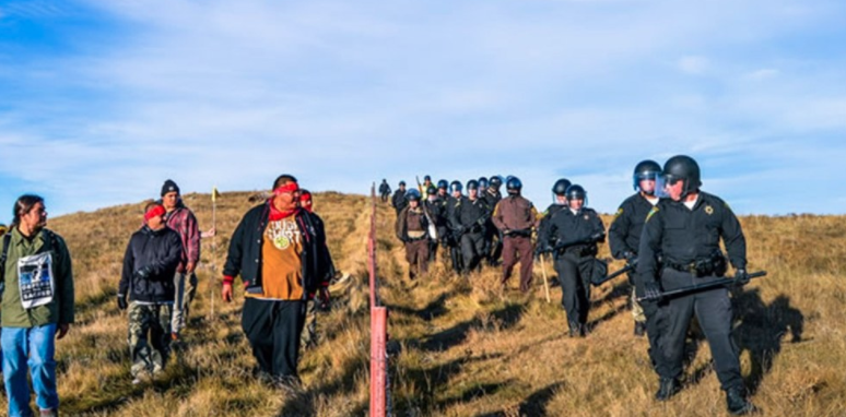 Water protectors and state security personnel faced off across a fence near the Dakota Access Pipeline construction site.Rob Wilson / Facebook