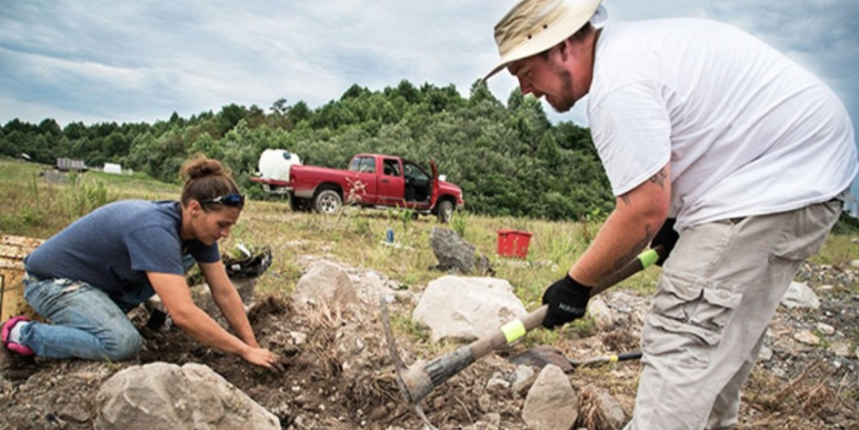 Crew members Eva Jones and Chris Farley, residents of Mingo County, work the soil. It is compacted, composed of blasted rock, and lacks organic matter.Paul Corbit Brown / YES! Magazine