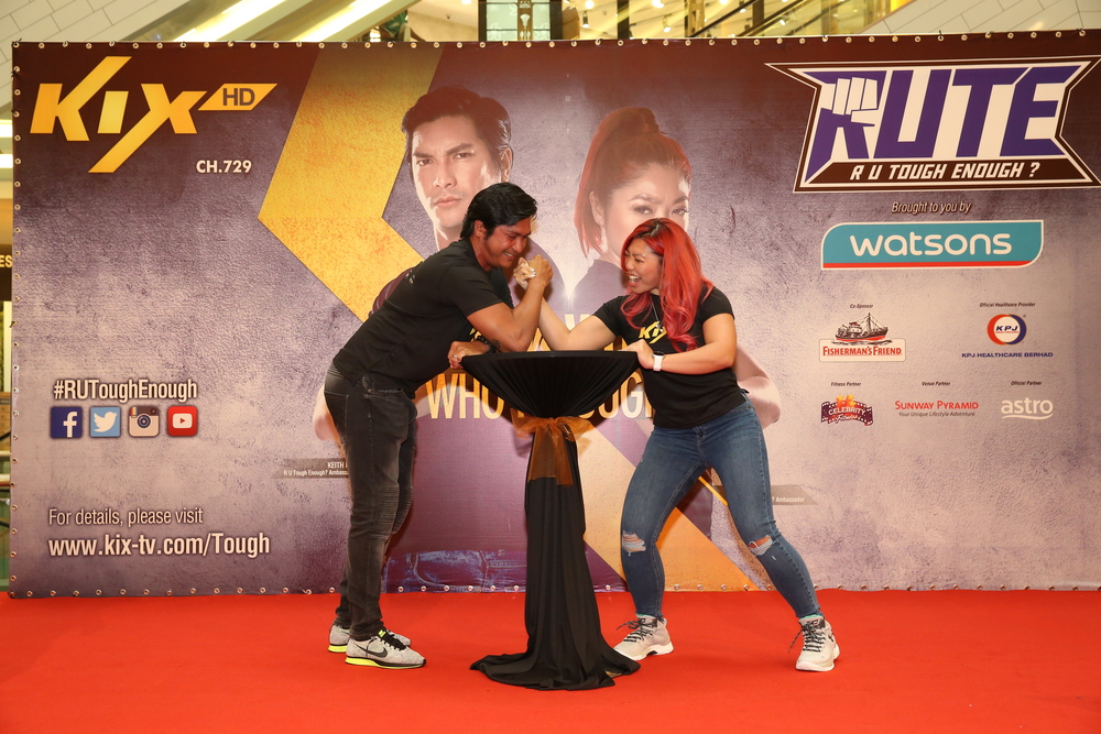 Keith Foo engages Linora Low in a friendly arm wrestling match.