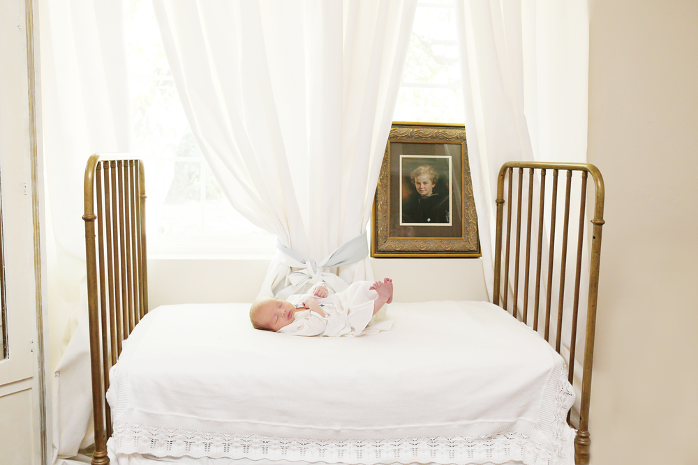 Arizona newborn photography session with family antiques. Newborn baby boy poses on family antique crib in front of heirloom family photo. Family generations newborn photography. Newborn photography sessions that are in your home in Scottsdale, AZ.