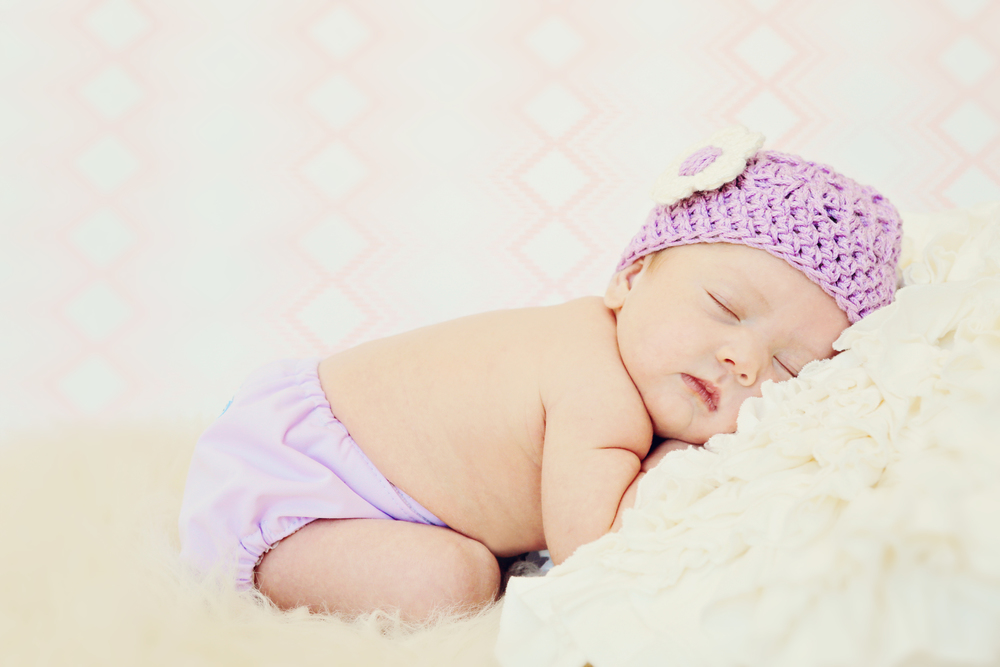Classic newborn session with baby girl in purple knit hat and diaper cover. Spring newborn inspirations.