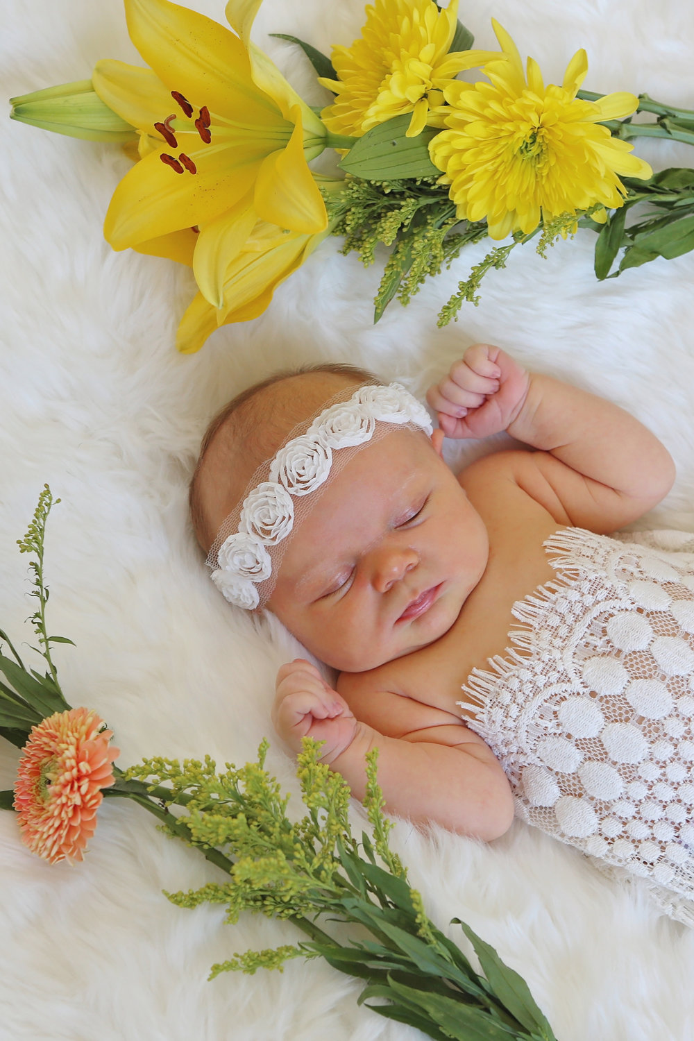 Newborn girl in crochet lace wrap and white headband in fresh yellow and coral flowers.