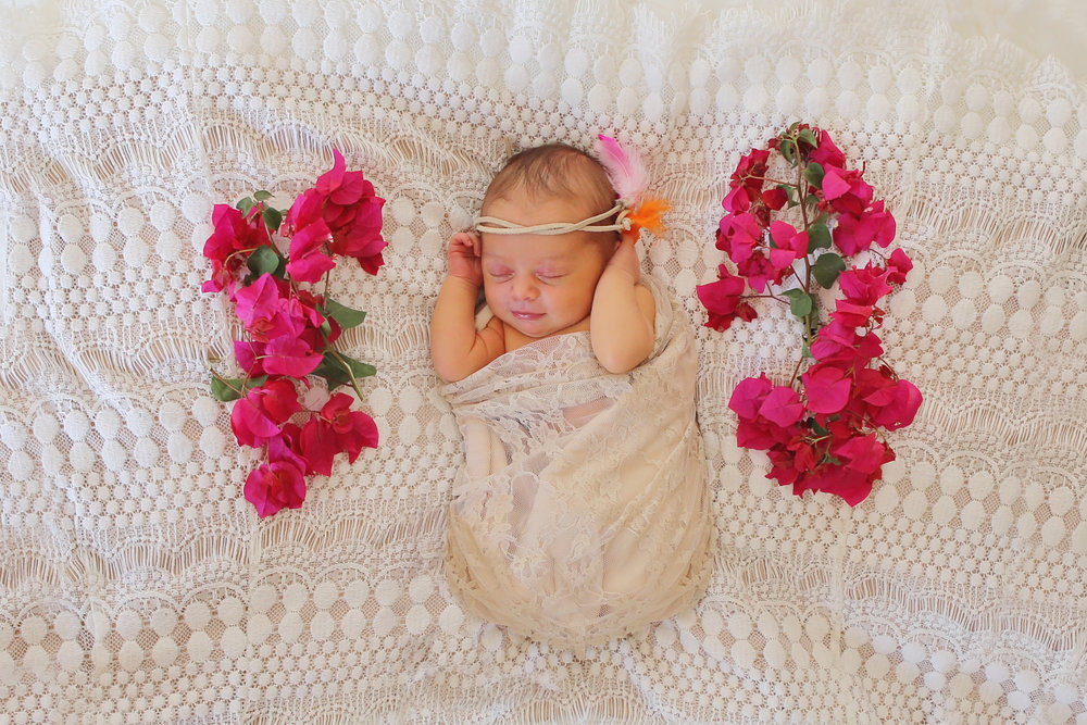 Newborn baby girl swaddled in a lace wrap with a feather head wrap next to flowers.