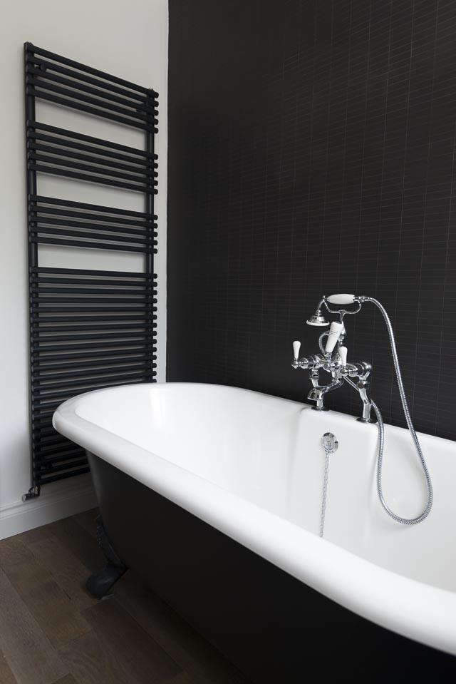Black Tiled Wall with Black Towel Rail and Roll Top Bath