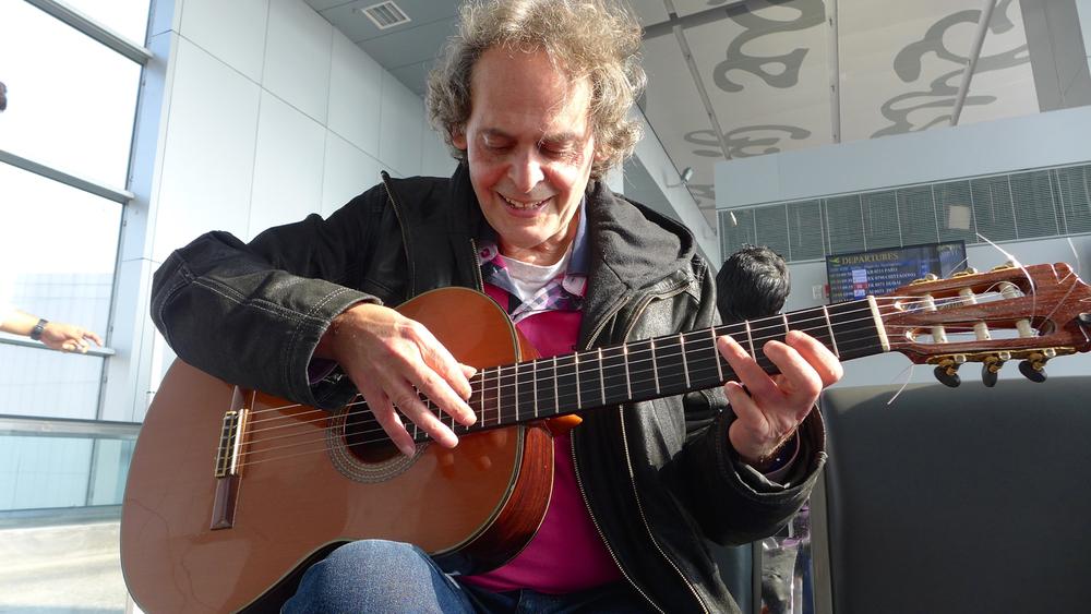 Roland Dyens spelar på gitaren min, medan vi ventar på flyet.