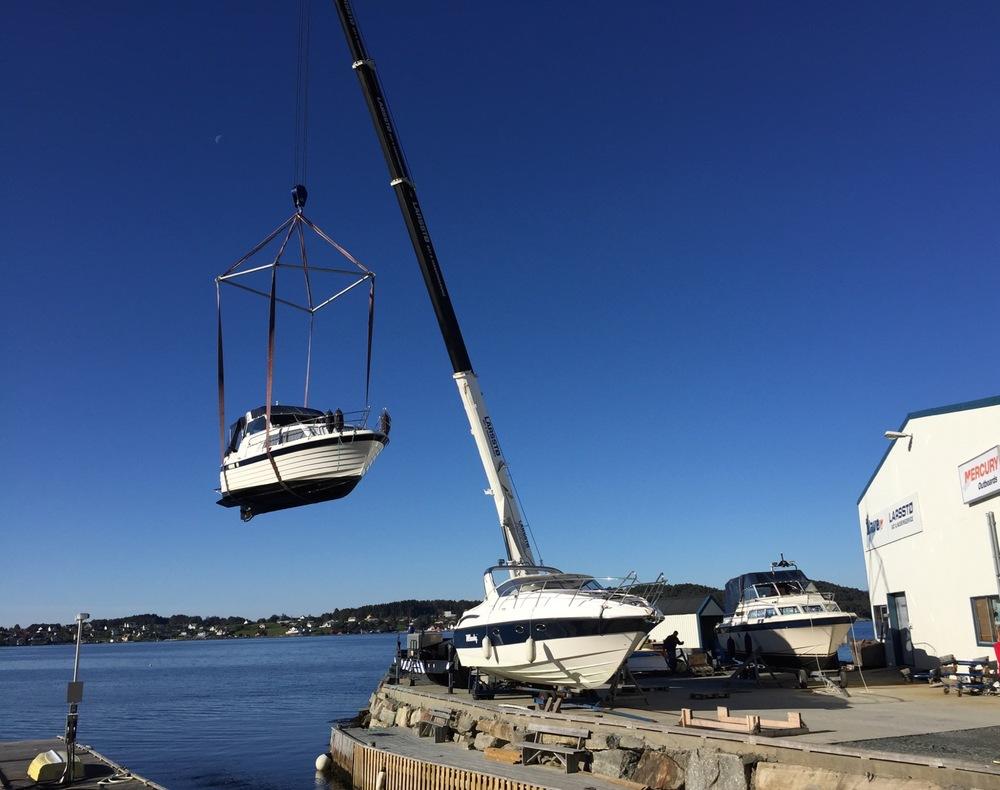 Ein stor krane løfter båtane på land.