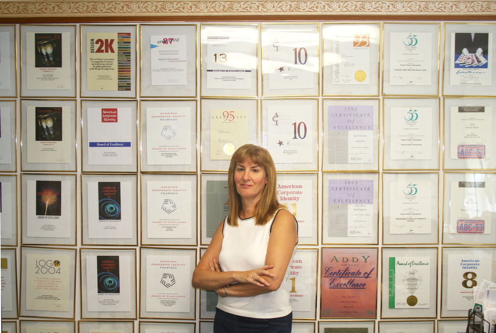 Randi in front of a wall of her awards.