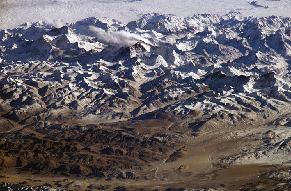 The perspective is illustrated by the summits of Makalu [left (8,462 metres; 27,765 feet)], Everest [middle (8,848 metres; 29,035 feet)] , Lhotse [middle (8,516 metres; 27,939 feet)] and Cho Oyu [right (8,201 metres; 26,906 feet)] -- at the heights typically flown by commercial aircraft.