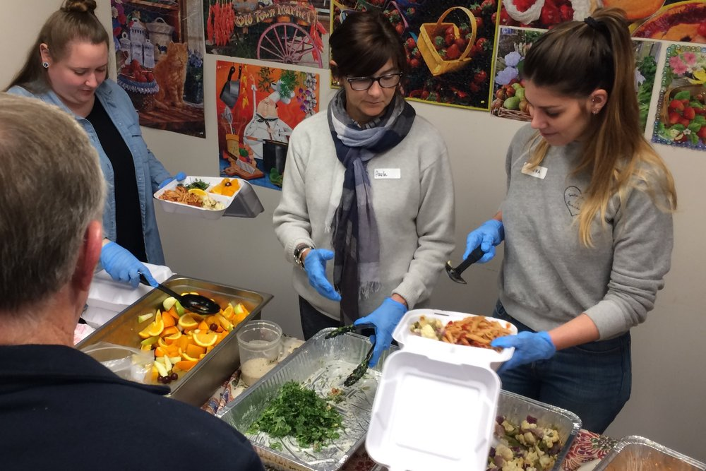 Paula (center) serving kale salad at John Glenn & Peggy Ann Residential Housing.