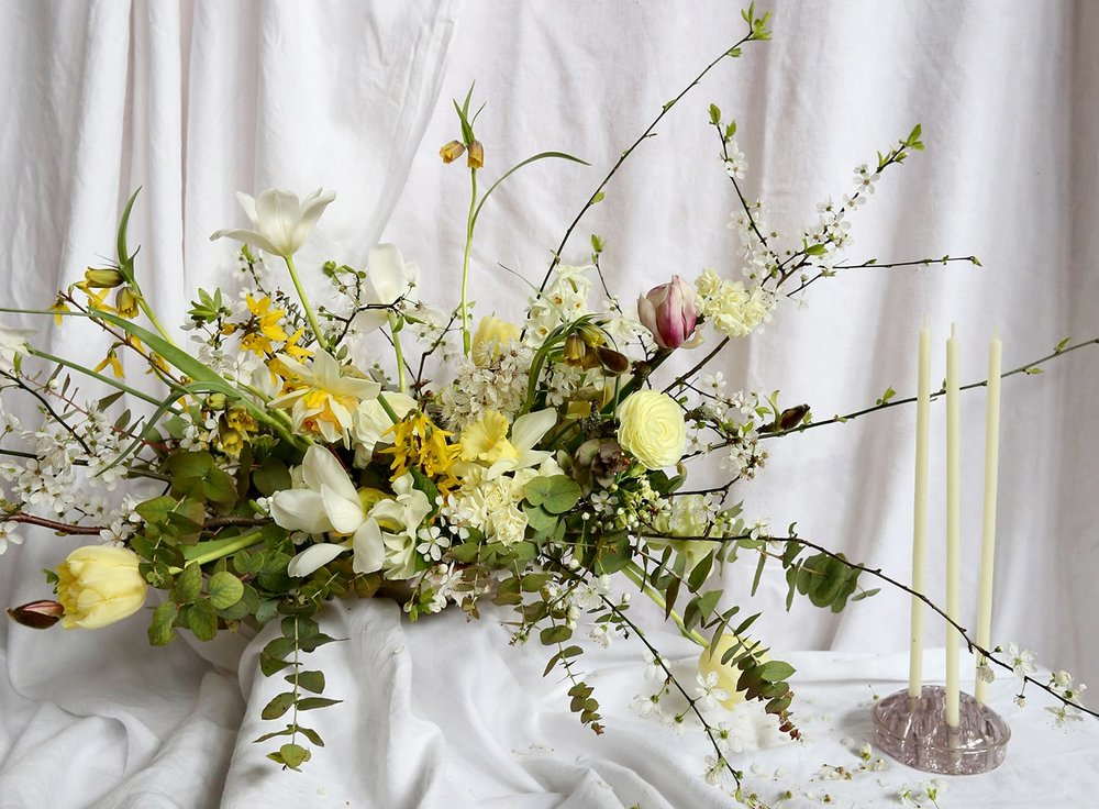 Yellow spring wedding table centrepiece with tulip and daffodils