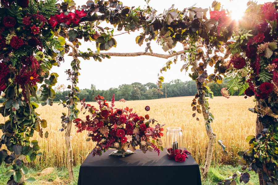 unique autumnal wedding archway and arbour with red flowers