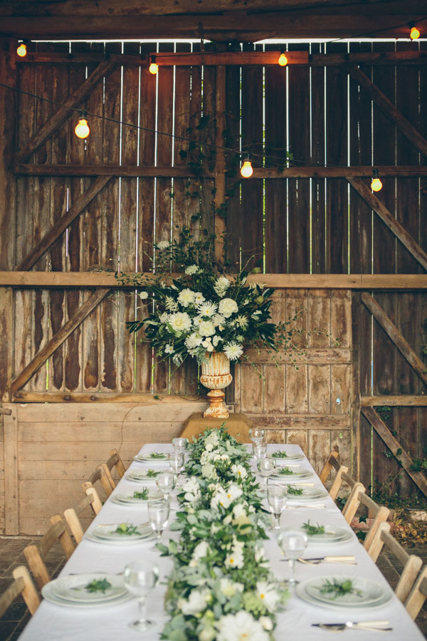 rustic unique barn wedding in summer with whiet flowers and table garland