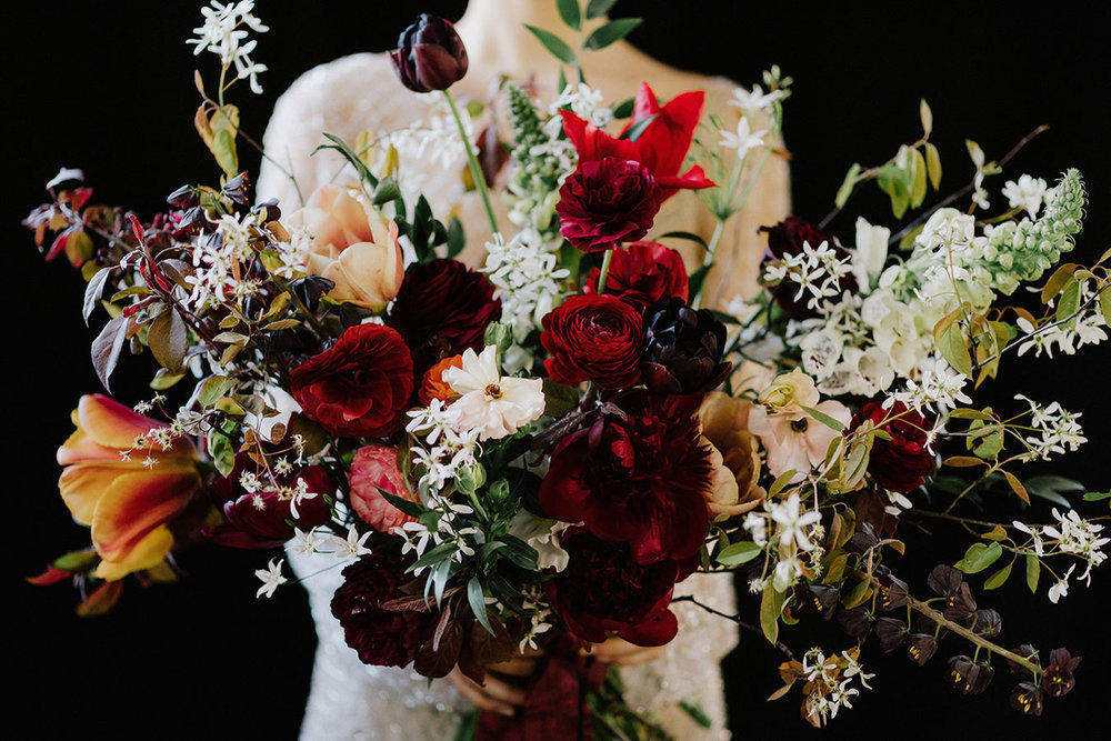 LArge dark adn moody spring bridal bouquet with ranuculus tulips and blossom.