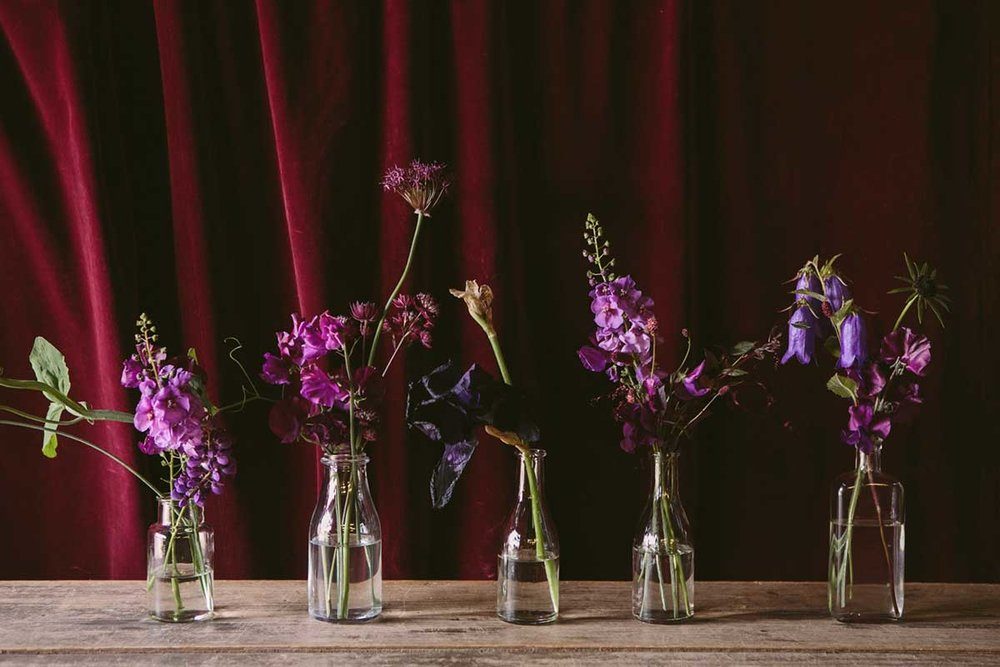 wedding flower bottles with summer flowers and foliage