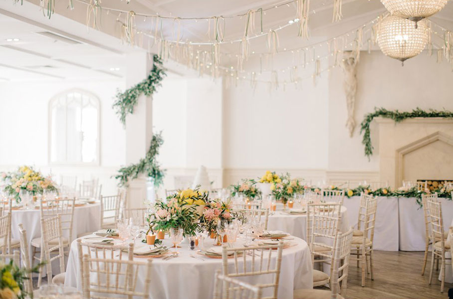 unique pastel coloured reception flowers with garlands and lemons at a summer wedding