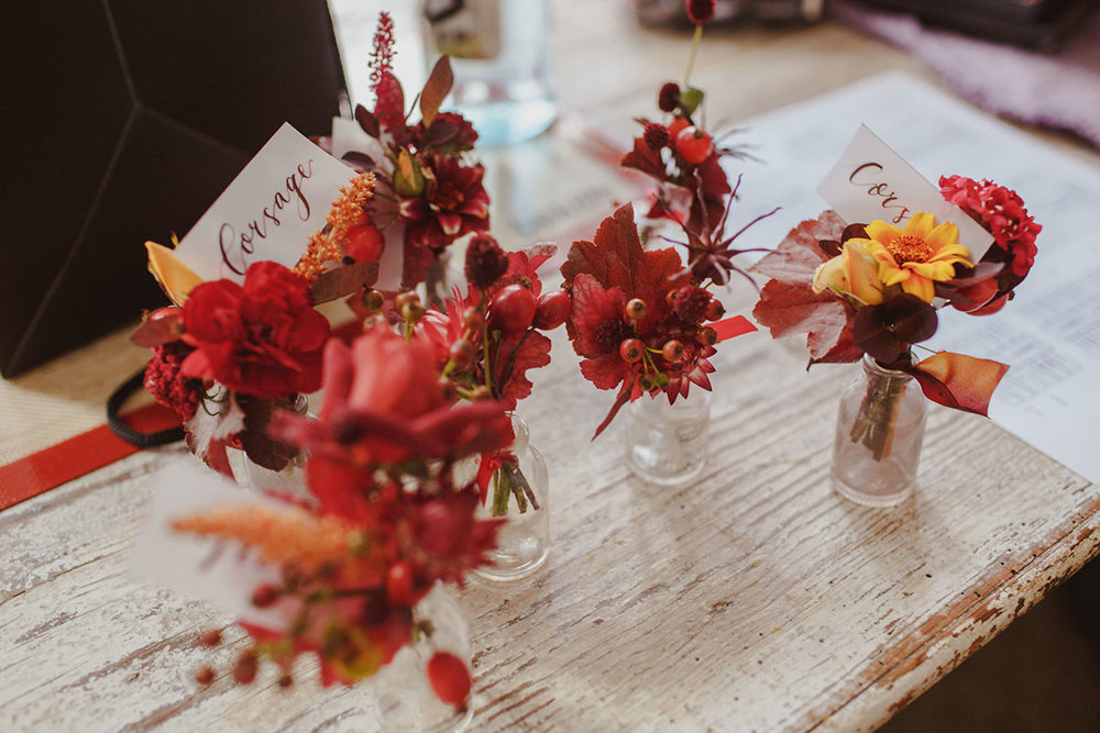 unique red and yellow buttonholes with wild flowers and berries