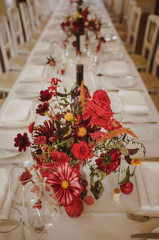 unique red and gold wedding table centres with wild flowers and vines