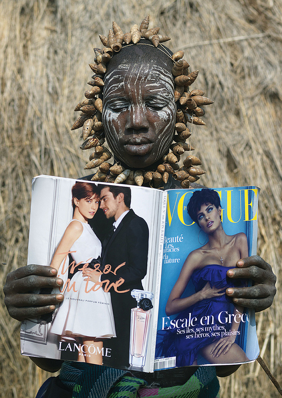 umsiko: Mursi tribe woman reading vogue magazine - omo valley Ethiopia Eric Lafforgue