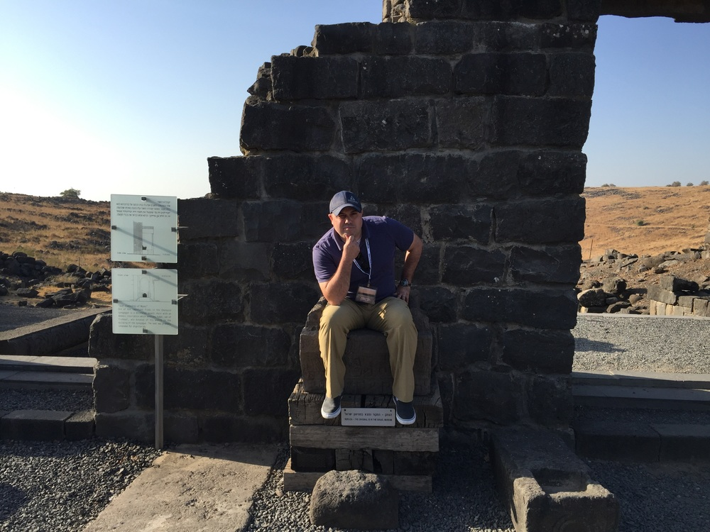 Sitting in a replica of Moses' Seat on the inside wall of a 3rd century tabernacle in Bethsaida.