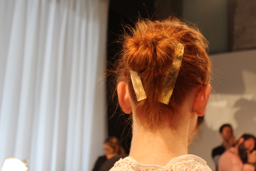 Ballerina buns with slashes of metallic sparkle were created backstage by Brent Lawler for Rene Furterer.
