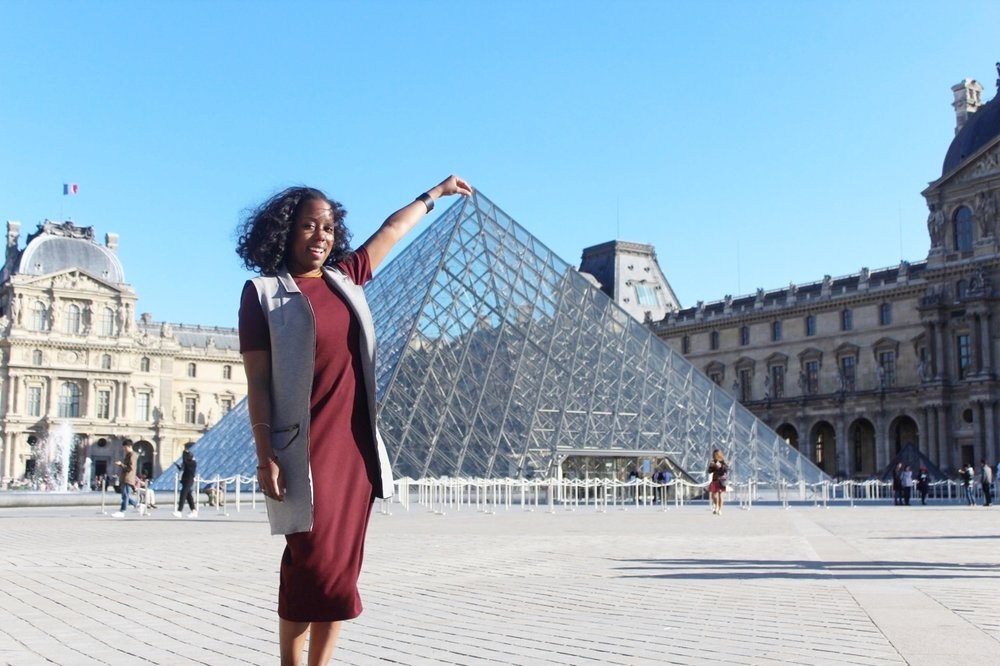Pinching the top of the Louvre Pyramid in the main courtyard of the Louvre Palace in Paris.