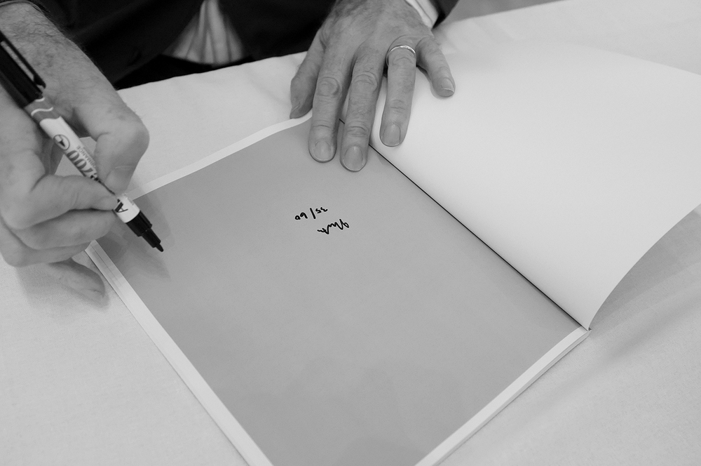 Ian North signing and numbering  Felicia: South Australia 1974-1978  on the occasion of its public launch at Australian Centre for Photography, Sydney, 20 April 2013. Photo: Pedro de Almeida.