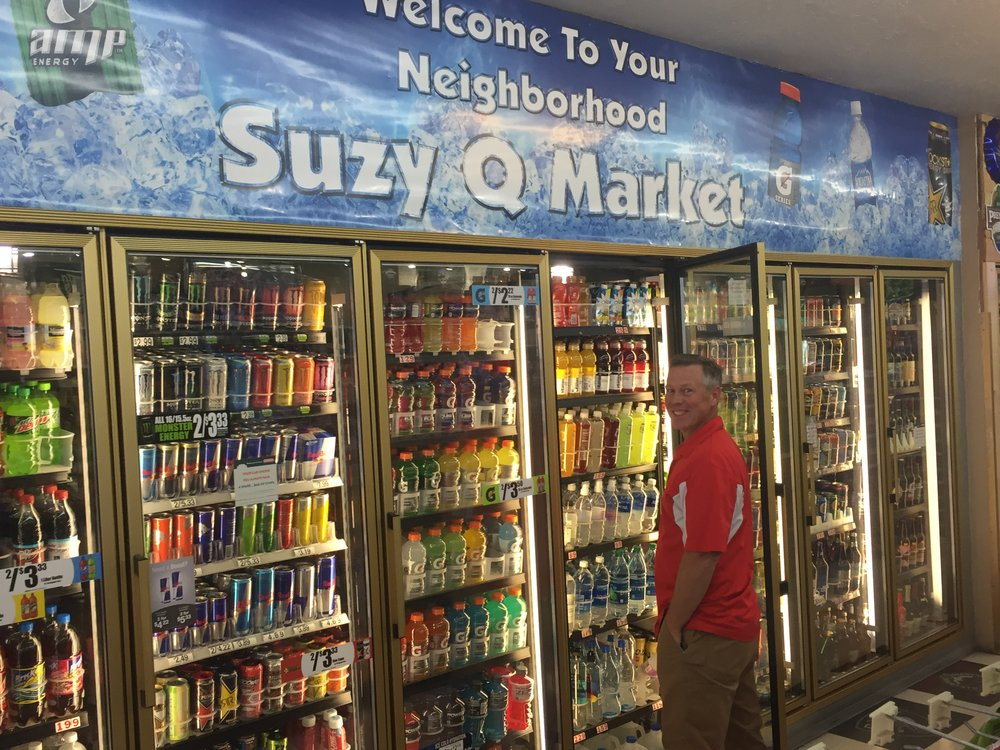 Owner, Rob Harrison, standing in front of one of his long drink coolers in the Suzy Q Market in Cottonwood, Arizona