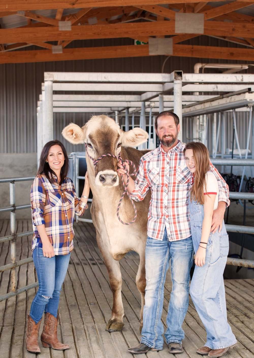 "Rick Anglin (center) with his wife Kristin (left), youngest daughter Macy (right), and Sue, a Brown Swiss who Rick says is ""kinda a diva."" Picture credit: Julie DeMarre of Edible Baja Arizona magazine."