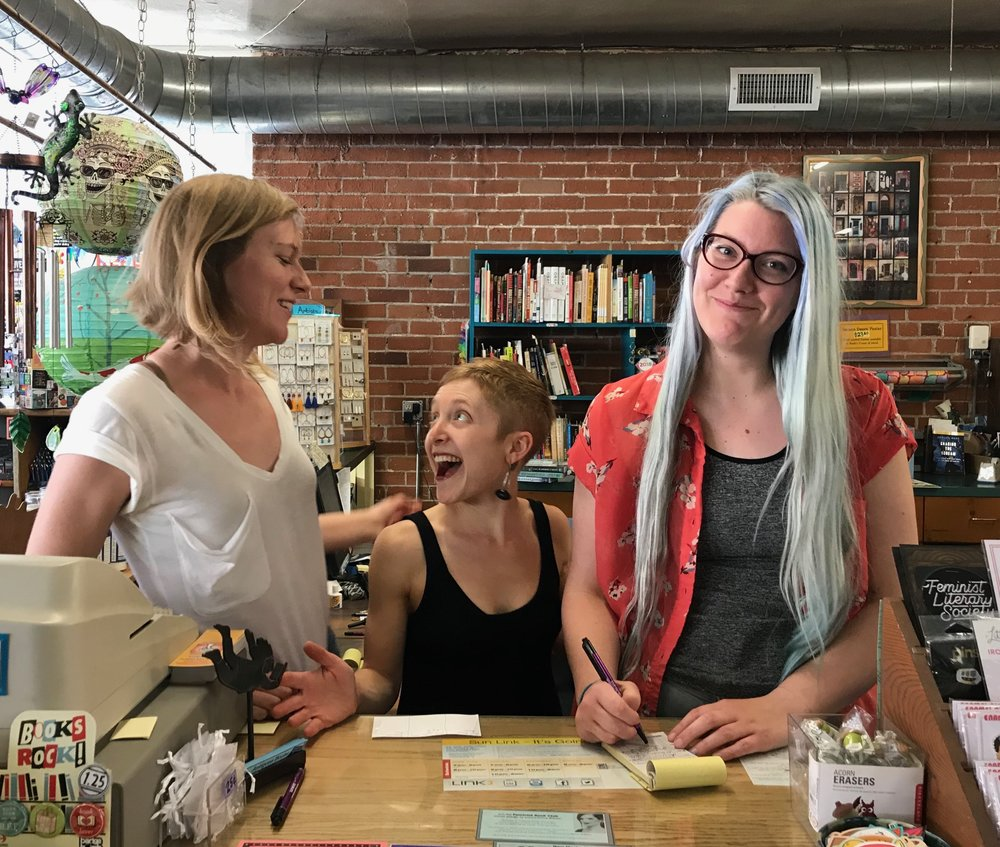 (Left to right) Morgan Miller, Kate Stern, and Melissa Negelspach stand behind the counter at Antigone Books in Tucson, Arizona. The three staff members are slated to take ownership of the independent bookstore in May.
