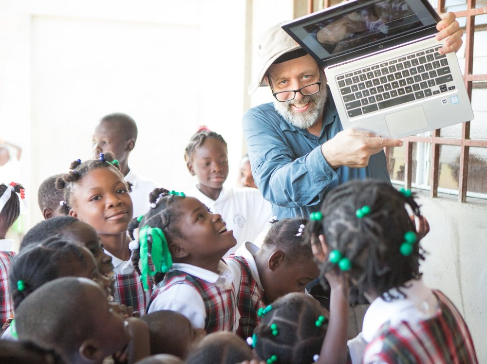 "Scott Grosse, public health economist, Atlanta  ""Educating and empowering girls (and boys) is perhaps the best long-term investment in community health. I was attracted to the opportunity to contribute to a new school built by and for Haitians and run on sustainable principles. A bonus was the goat project! My PhD research project found that children in farm households in Africa are healthier and grow better if there is a goat in the household. In 3 trips to the EcoVillages since 2013 I have been privileged to see a school take shape and blossom and to see hope and joy on the faces of the children, parents, teachers, and community leaders."""