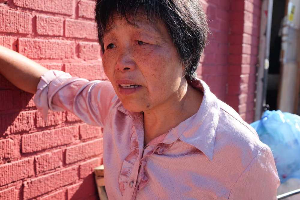 "Grandmother Cheng stands outside the 62nd Street recycling center. Cheng moved to New York 10 years ago from Fujian. She has a daughter and son and three grandchildren, but none of them live near her.  She feels a lot of guilt that she is unable to take care of her grandchildren, a role most Chinese grandmothers are expected to take on. She also complained that she is not a good cook; being number five of seven siblings meant her older sisters did all the cooking. ""Even at my age I still don't know how to make  zhongzi  [sticky rice wrapped in bamboo leaves for special occasions]."""