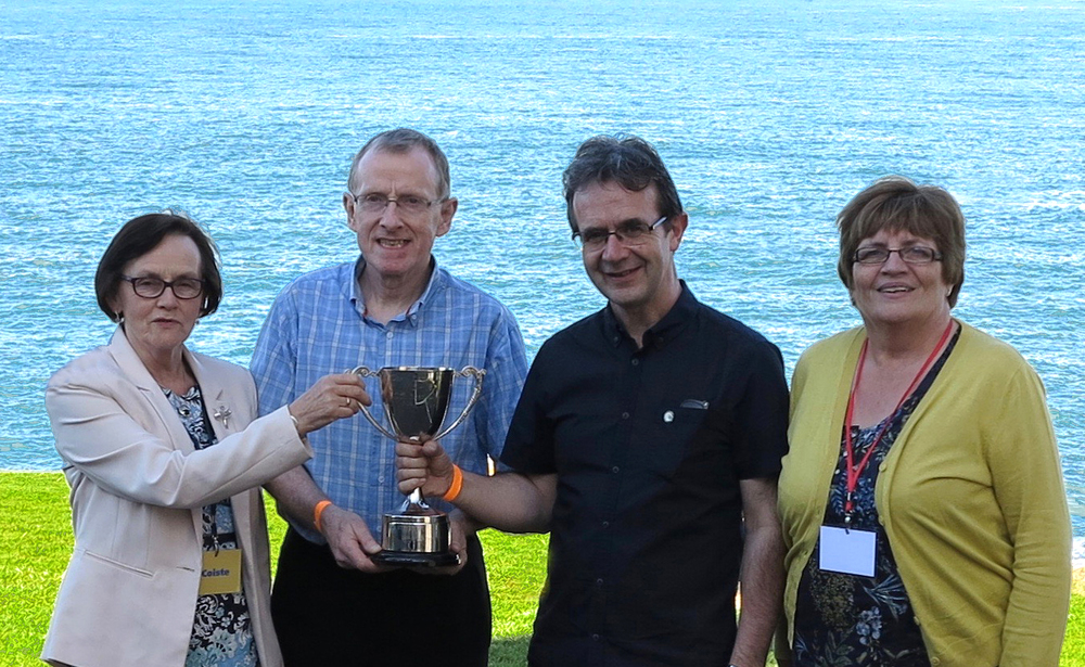 Mary Whelan and Helen O Sullivan present the U18 Céilí Band trophy to tutors Mick Glynn and Martin Gaffney of Craobh Naithí