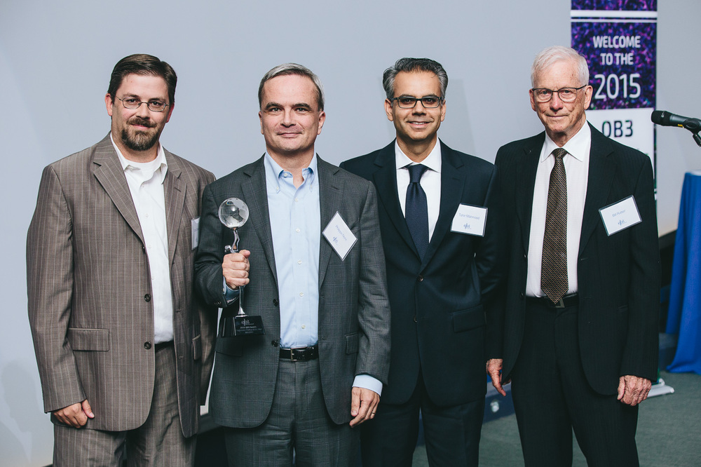 Philippe Nore (holding trophy) and the MiNDERA team accept the award for Diagnostics Startup of the Year from Bill Rutter (R)
