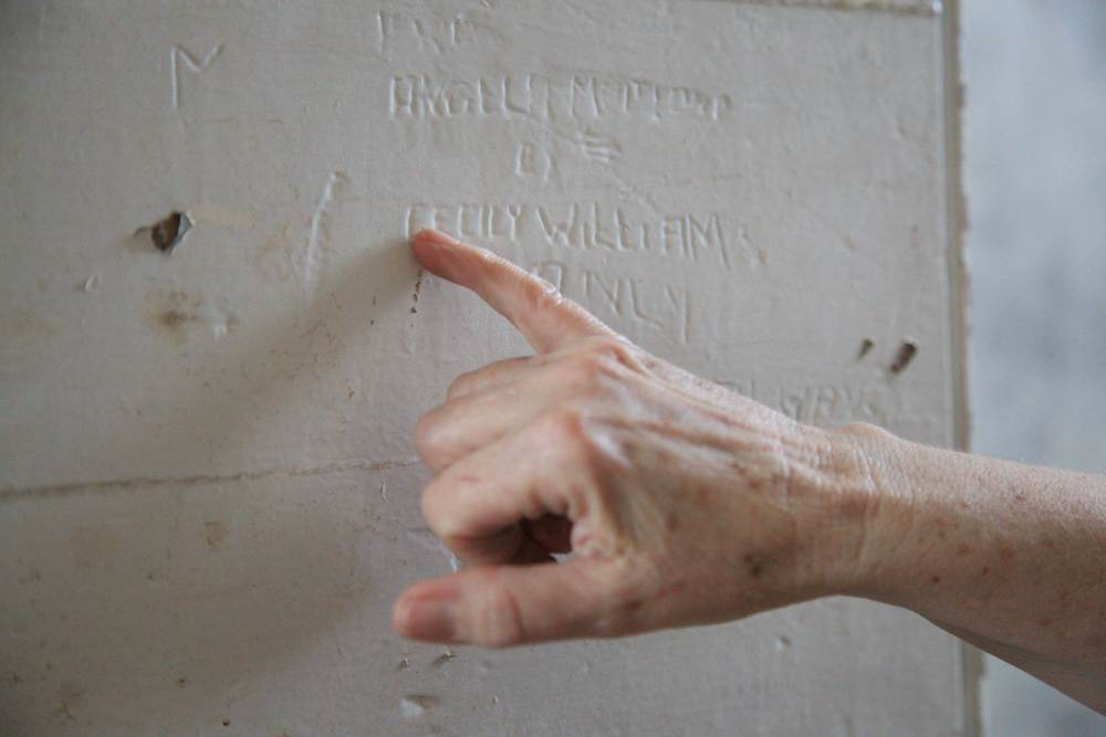 A hand points out the name Cecily Williams carved into a wall among other graffiti.