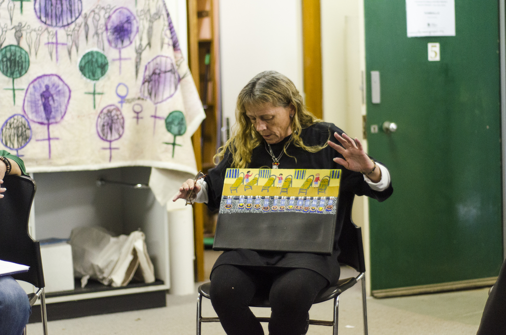 A participant speaks about her work during Lily Hibberd's painting workshop.
