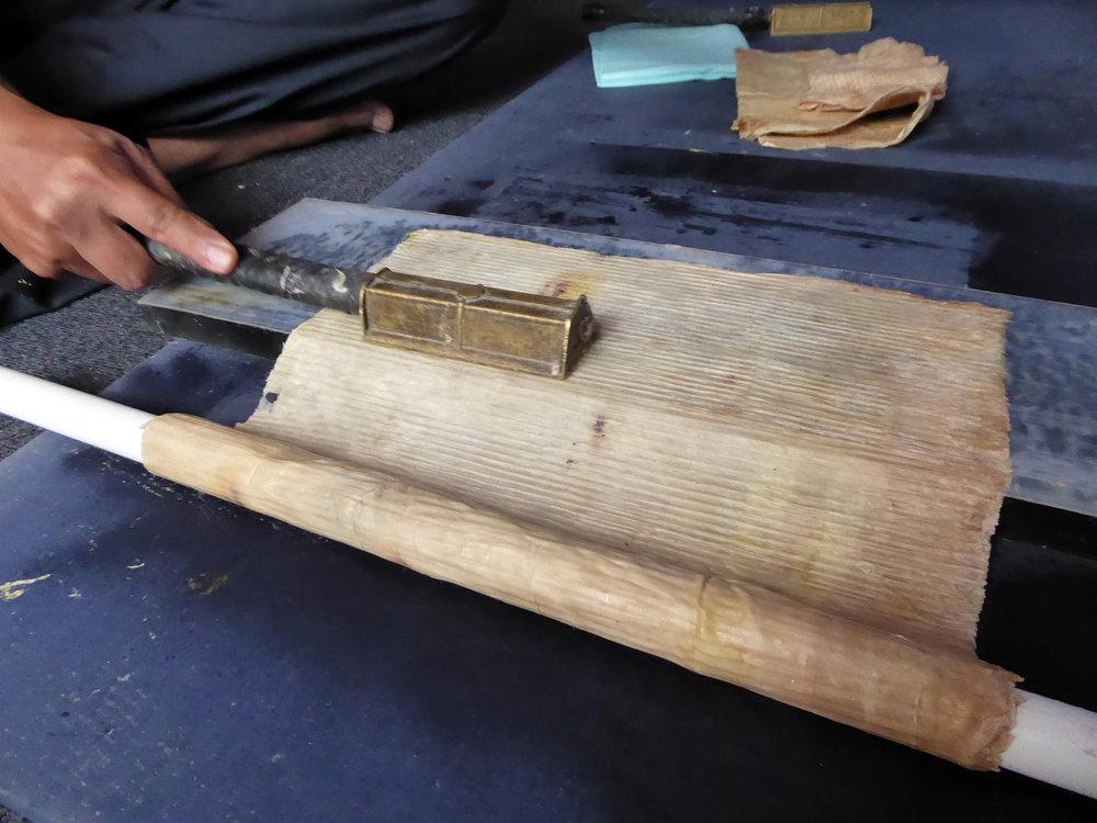 Pak Tedi Permadi demonstrating daluang beaten bark papermaking near Bandung, Java.