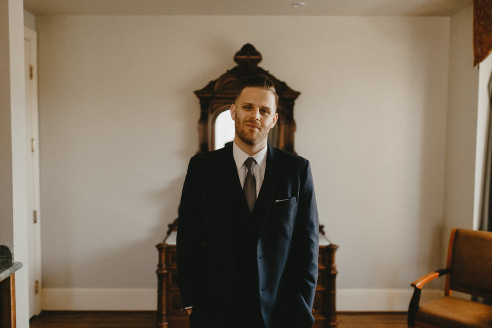 a portrait of a groom in a suite at hotel diamond