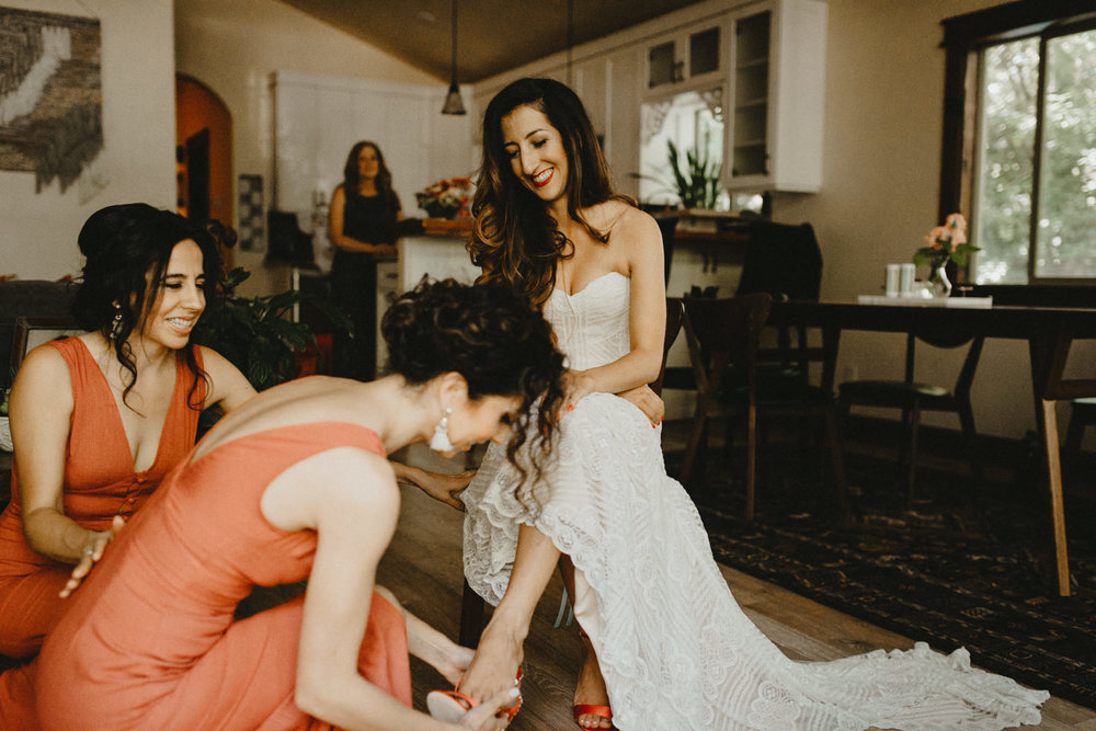 sisters help the bride get her shoes on