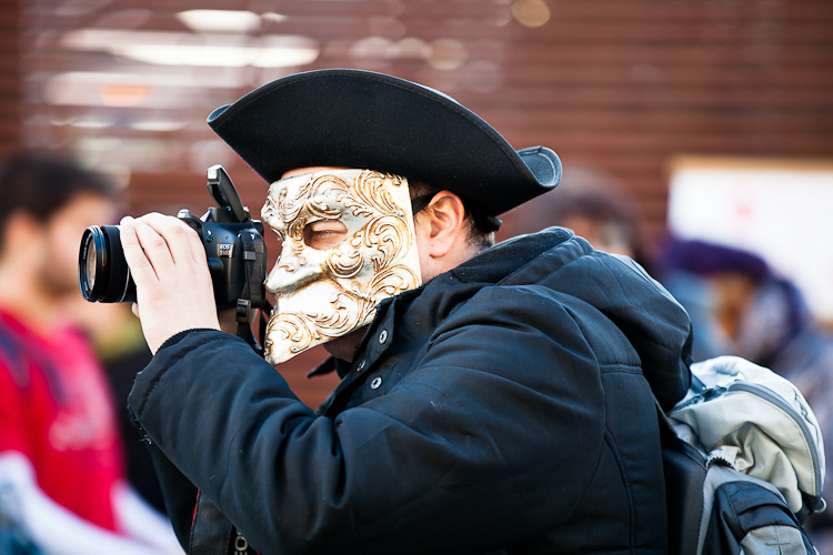 Person in Venetian costume during Venice Carnival taking a photograph