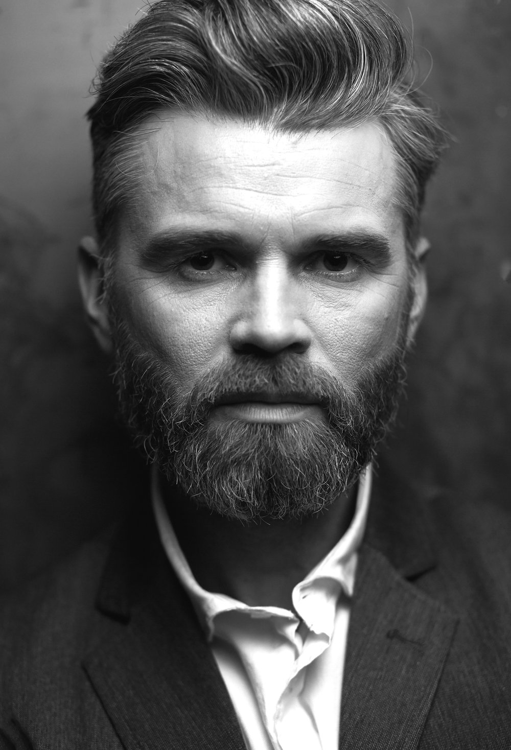 Closeup portrait of handsome beautiful serious man with beard, wearing white shirt and black waistcoat, posing in studio on dark grey background in black and white
