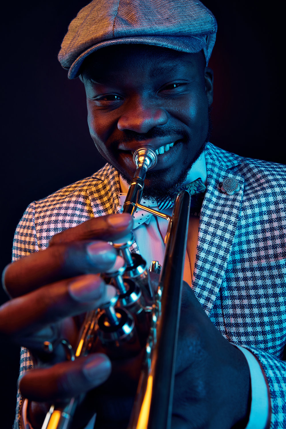 Neon studio portrait of handsome smiling black man in plaid jacket and vintage cap with trumpet in his hands. Orange and blue light