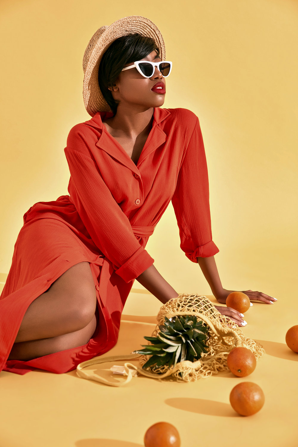 Studio shot of young black woman with short hair and big red lips dressed in orange dress straw hat and shoes and white sunglasses set down near oranges and pineapple. Yellow background
