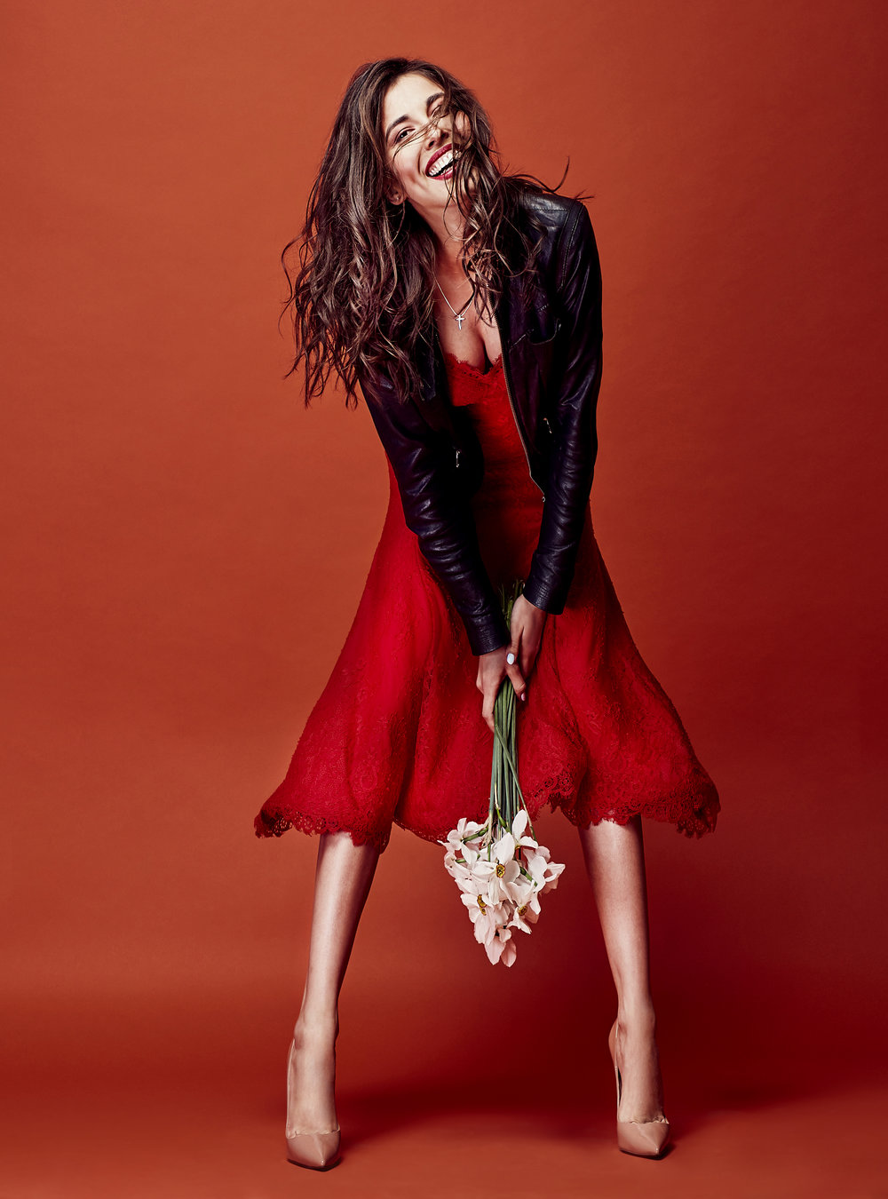 Beautiful smiling brunette woman dressed in red lace dress, black leather jacket and nude heels posing with bunch of daffodils in studio with orange background