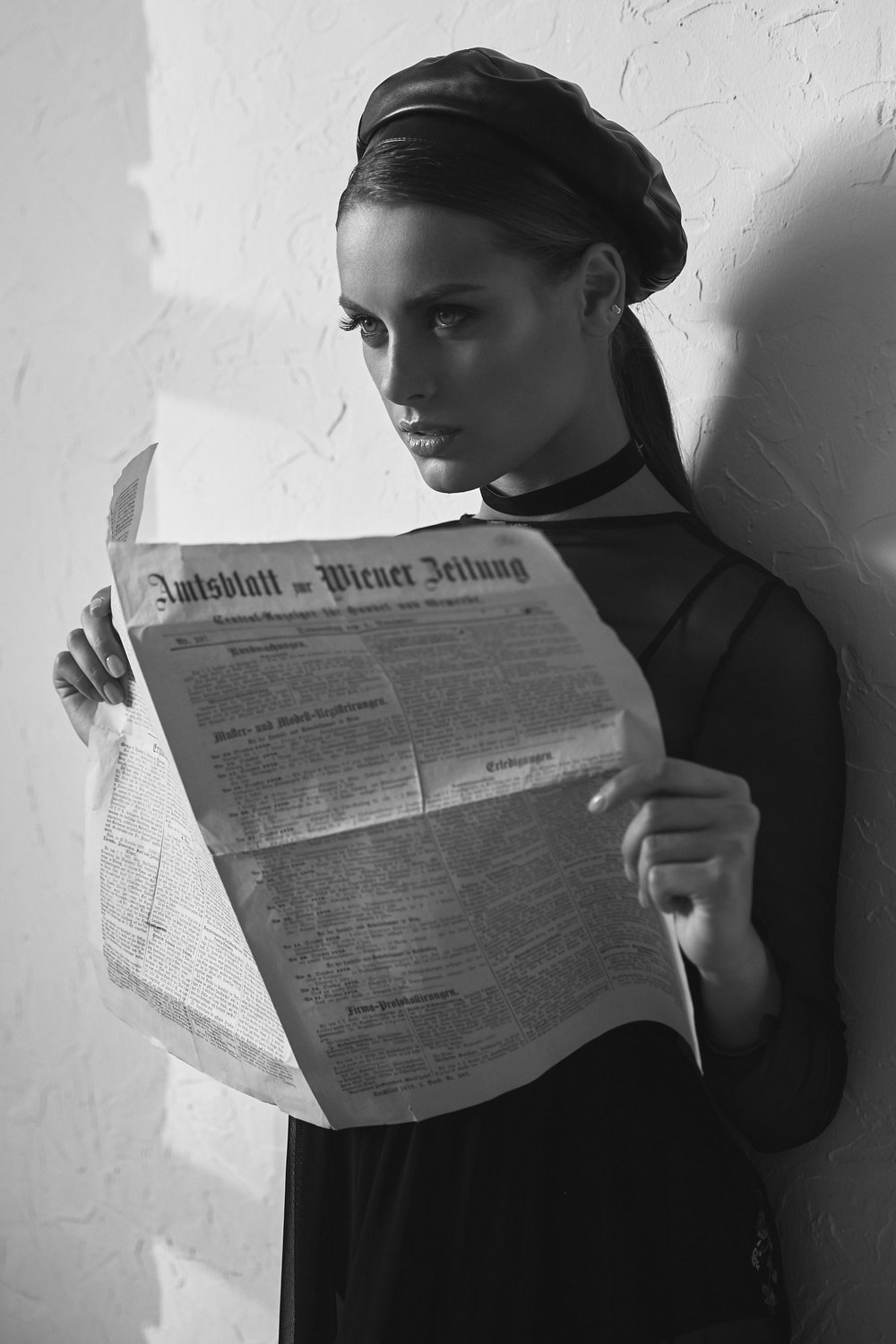 Black and white portrait of beautiful woman in newsboy cap with vintage newspaper in hands. Retro style