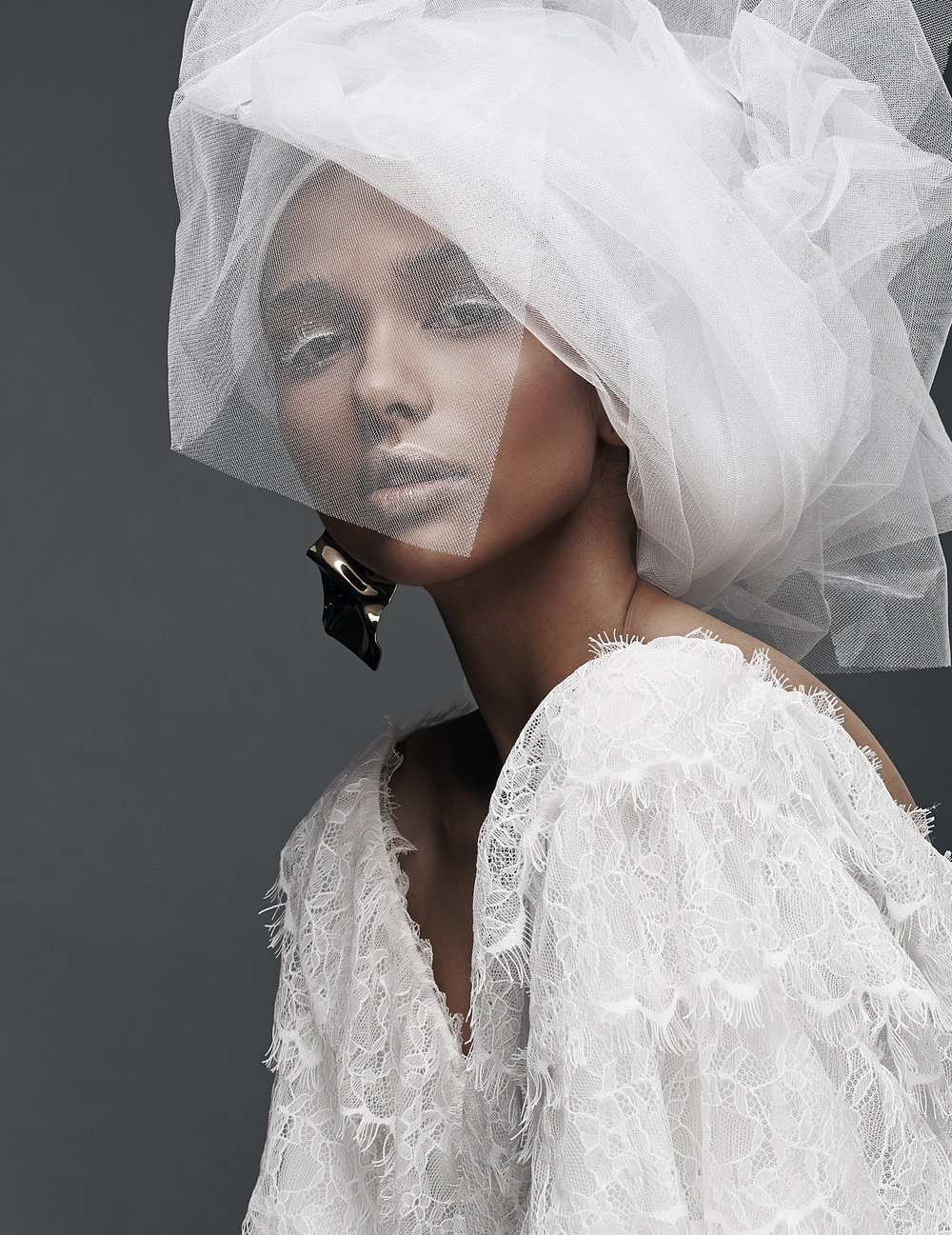 Studio portrait of woman with white make up, in white lace dress with white veil head tie and big earring.