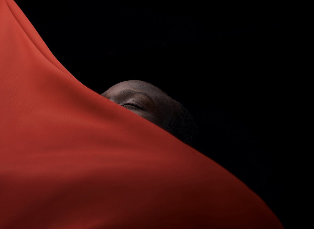 Art portrait of afro man. Man's head behind red fabric, black background. Dark key. Layers, lines, diagonal.